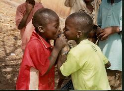 Two boys share a plastic bag of water they have purchased, in Africa.